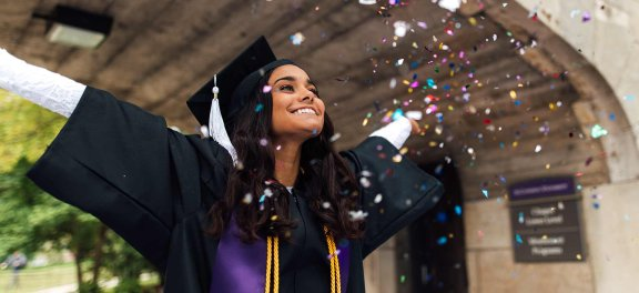 Girl graduate throwing confetti